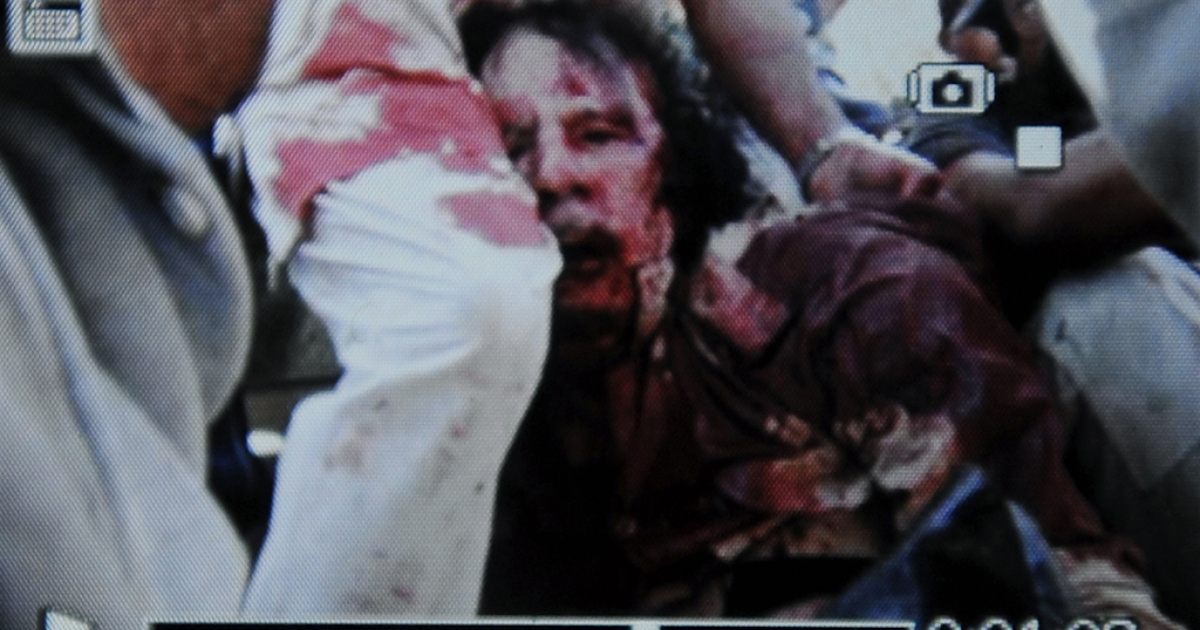 THE RISE AND FALL OF GADDAFI: An image captured off a cellular phone camera shows the arrest of Libya's strongman Moamer Kadhafi in Sirte on October 20, 2011.  A Libyan National Transitional Council (NTC) commander had told AFP that Kadhafi was captured as his hometown Sirte was falling, adding that the ousted strongman was badly wounded.</p>