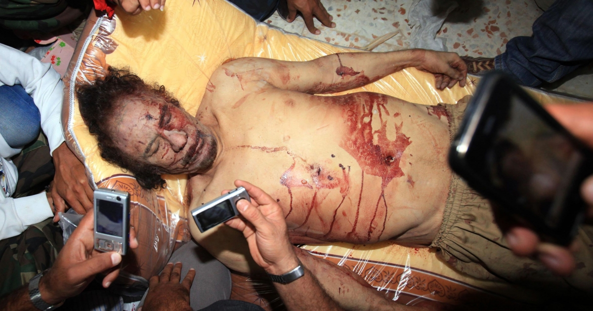 Libyans take pictures with their mobile phones of the body of Moamer Kadhafi in Misrata on Oct. 20, 2011.</p>