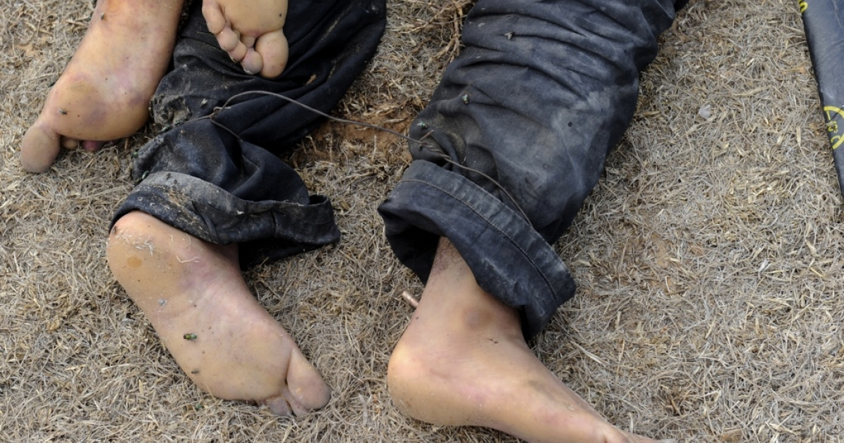 A picture shows the feet of men, believed to have been executed, lying dead in a field in the Libyan town of Sirte on October 22, 2011.</p>