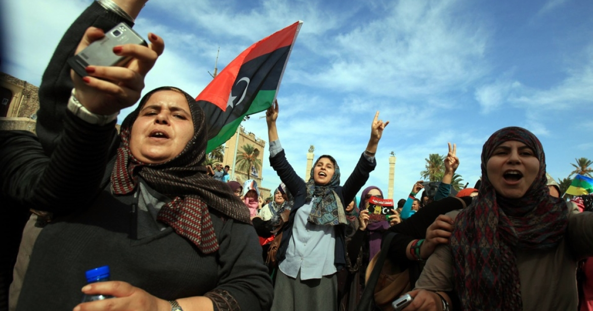 Libyans wave their new national flag as they celebrate in the streets of Tripoli following news of Muammar Gaddafi's capture on October 20, 2011.</p>