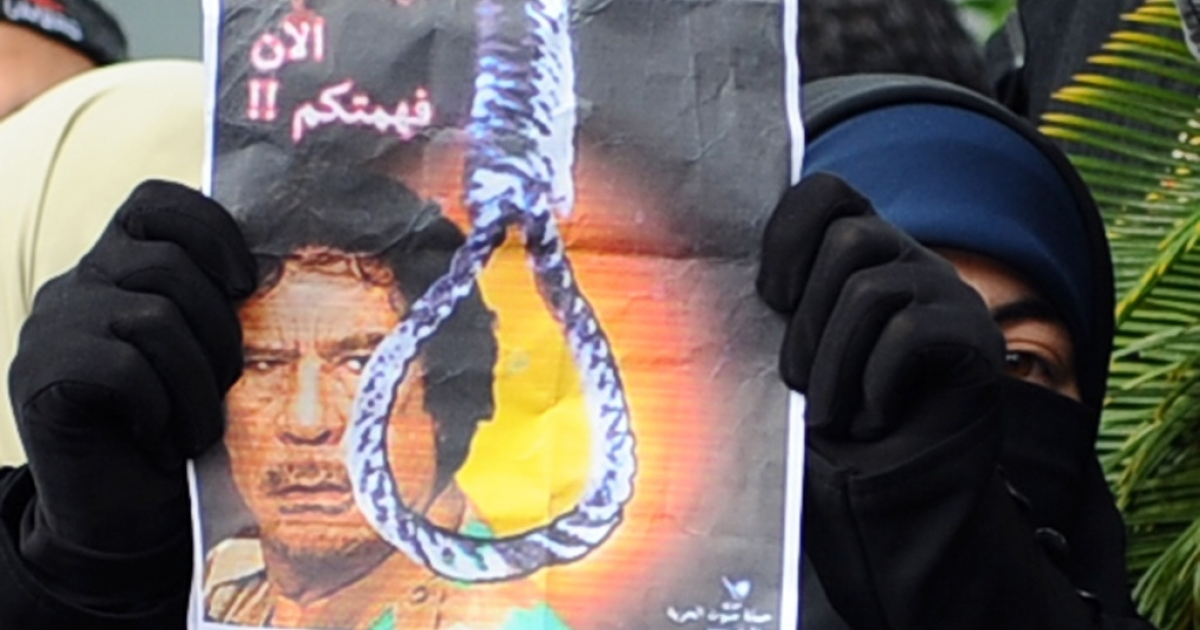 A Tunisian woman holds a picture showing a rope and a portrait of Muammar Gaddafi during a protest in front of the Libyan embassy in Tunis on Feb. 22, 2011.</p>