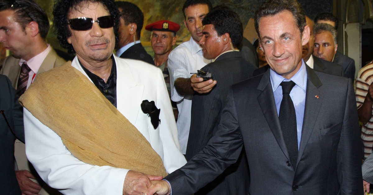Sarkozy shakes hands with Gaddafi in Tripoli upon his arrival for an official visit to Libya on July 25, 2007.</p>