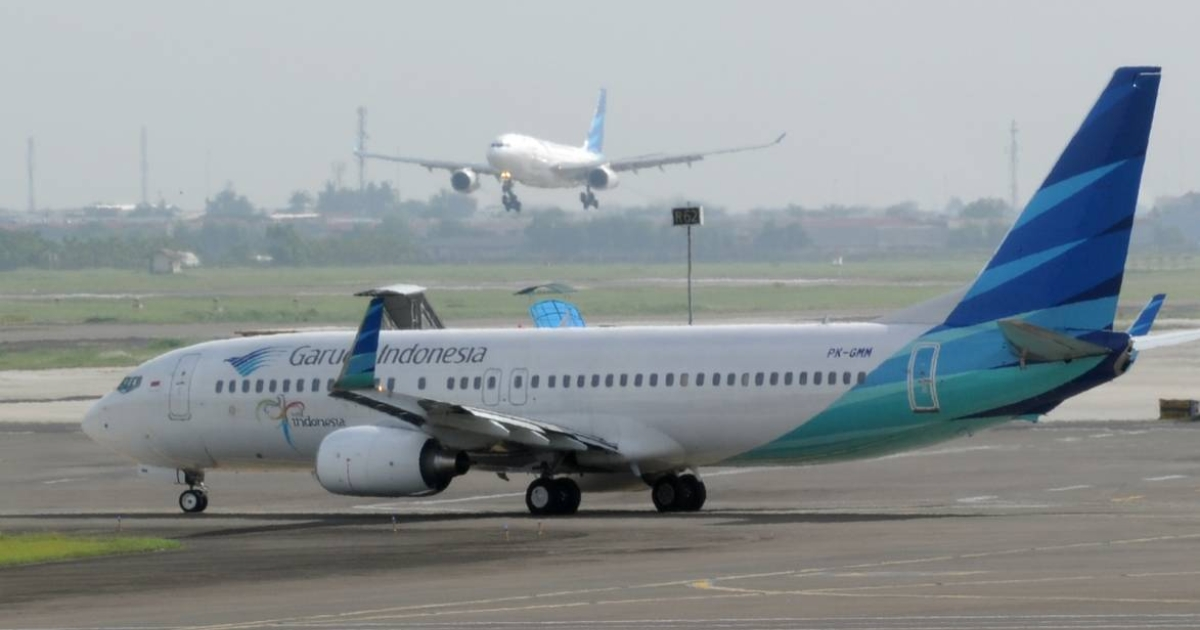 A Garuda Indonesia jet lands and another prepares to take off at Soekarno-Hatta airport in Jakarta.</p>