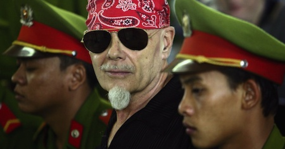 Disgraced glam rocker Gary Glitter is flanked by Vietnamese police as his guilty verdict for sex crimes is read at a courthouse in Ba Via, Vietnam, in 2006.</p>