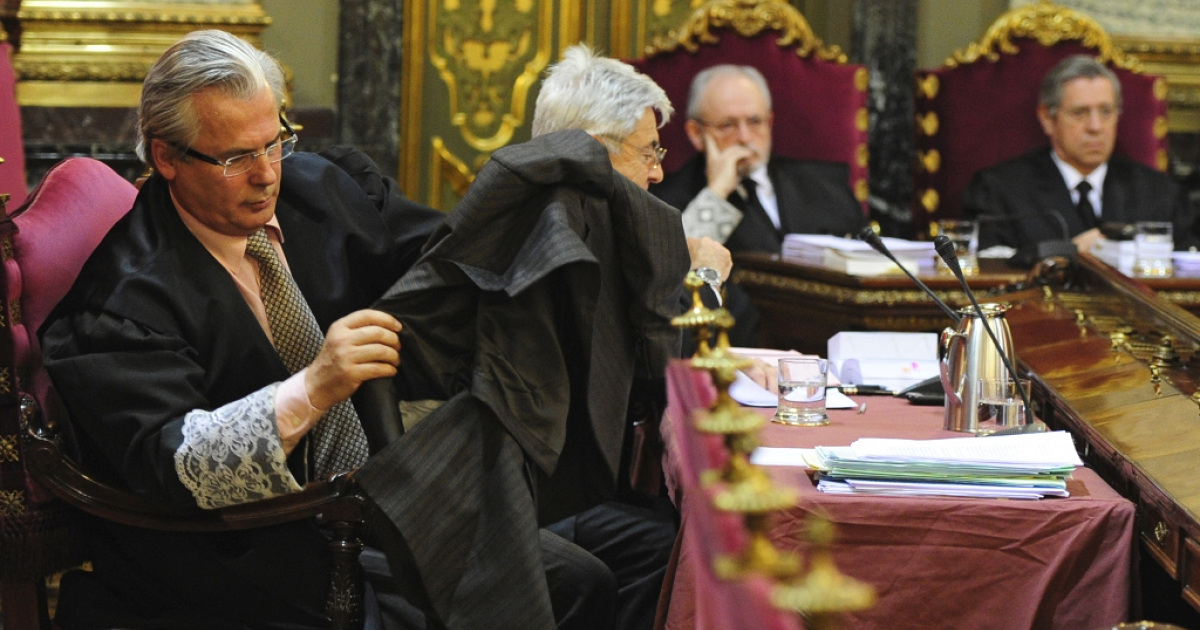 Spanish prosecuting judge Baltasar Garzon puts on his robes at the start of his trial today in Madrid</p>