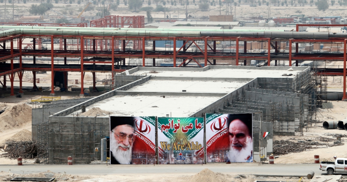A huge banner bearing portraits of Iran's supreme leader Ayatollah Ali Khamenei (L) and his predecessor, the founder of the Islamic Republic, Ayatollah Ruhollah Khomeini (R), is seen on a building being constructed at phase 15 and 16 of South Pars gas field development in the southern Iranian port town of Asaluyeh on July 19, 2010.</p>
