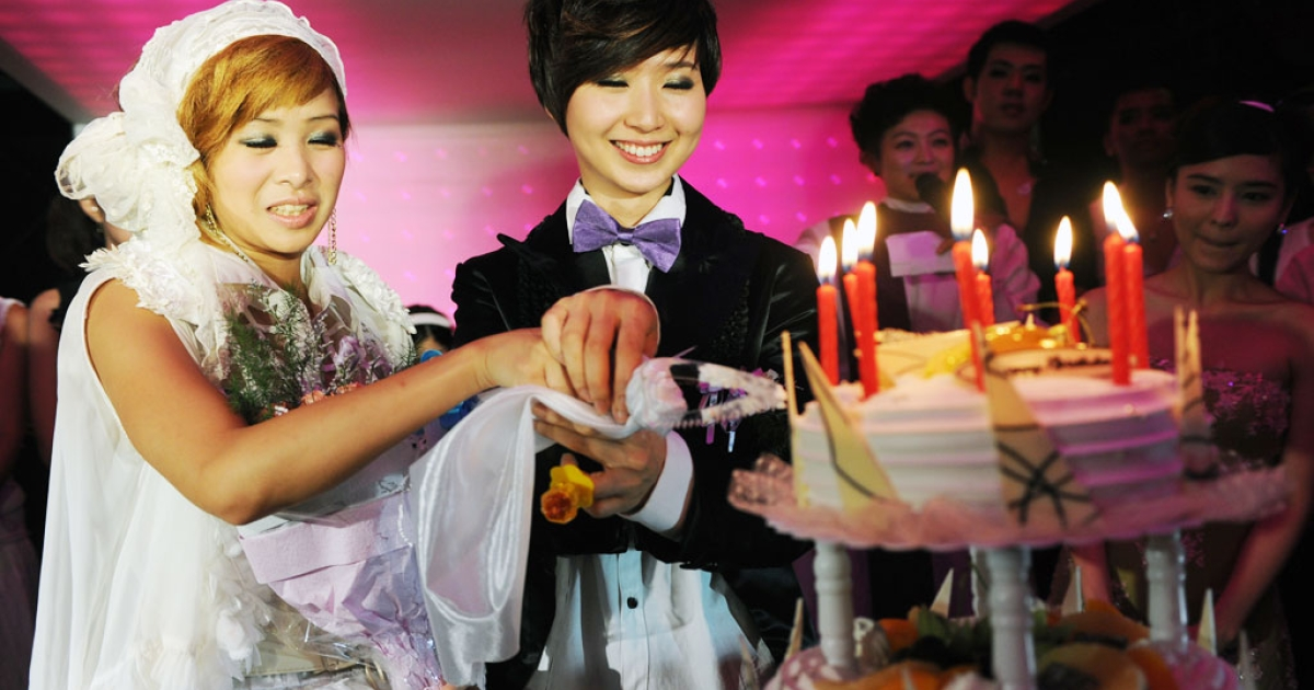 A same sex couple cut a cake during a mass 'wedding' party event in Taipei on August 21, 2011.</p>