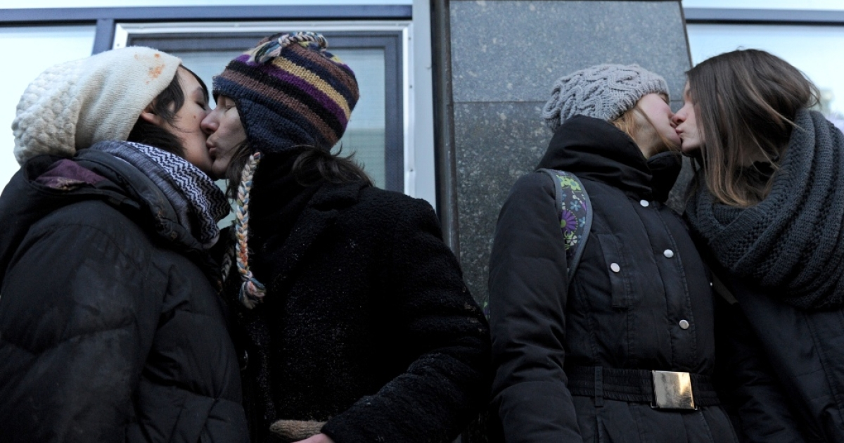 Russian gay rights activists kiss each other in front of Russian State Duma building on January 22, 2013 during their protest action in Moscow.</p>