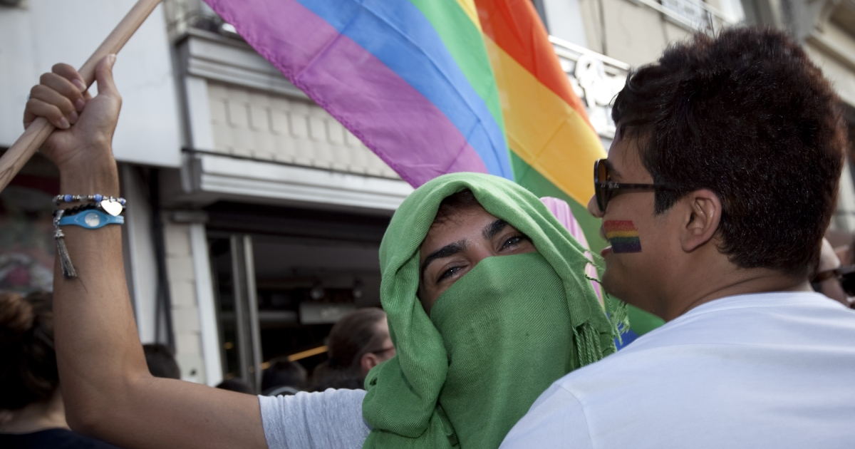 Holding a rainbow flag and dressed in hijab, an LGBT supporter makes a political statement at the Gay Pride March in Istanbul on June 19, 2011. Turkey is the only Muslim-majority country that permits such an event.</p>