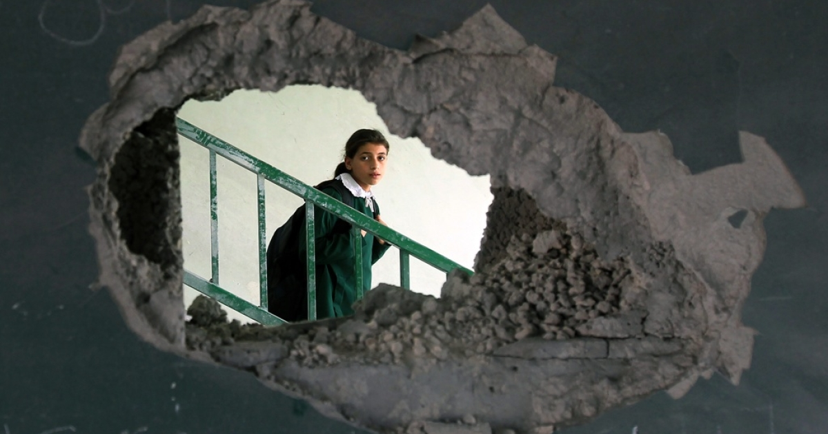 A Palestinian girl appears at her school, which was damaged in Israeli airstrikes.</p>