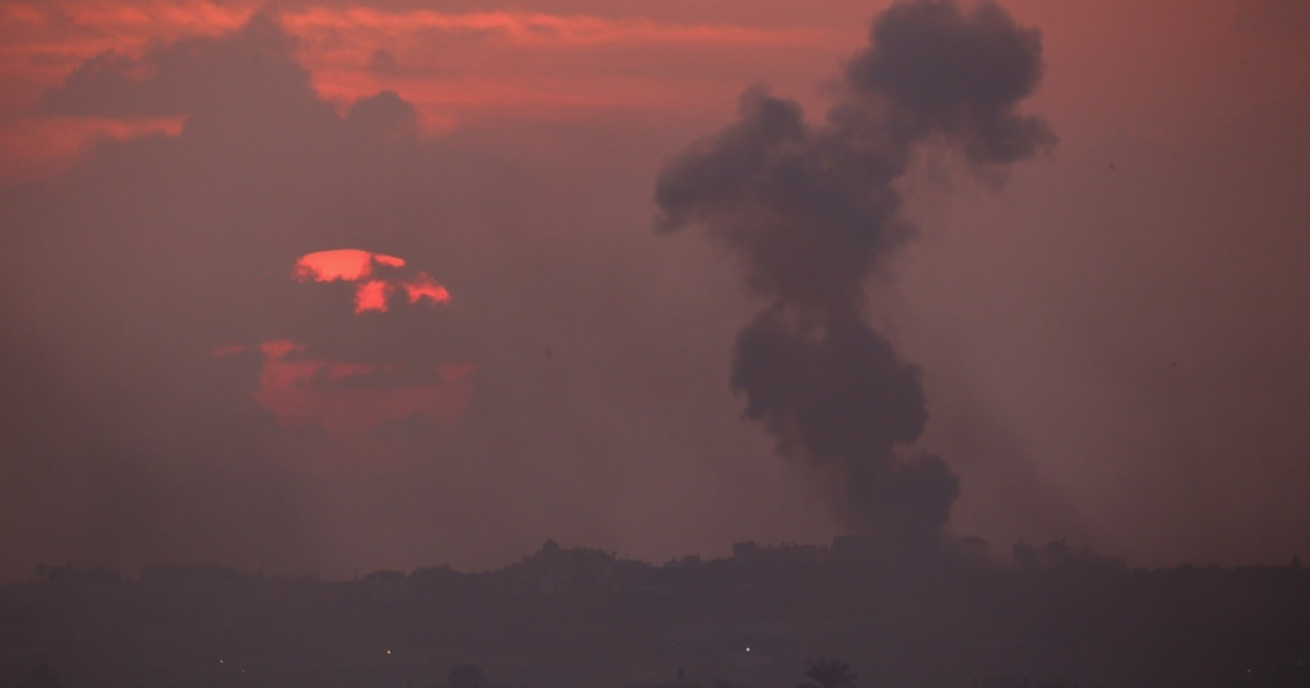 A plume of smoke rises above Gaza City at sunset after an Israeli airstrike on Nov. 19, 2012.</p>