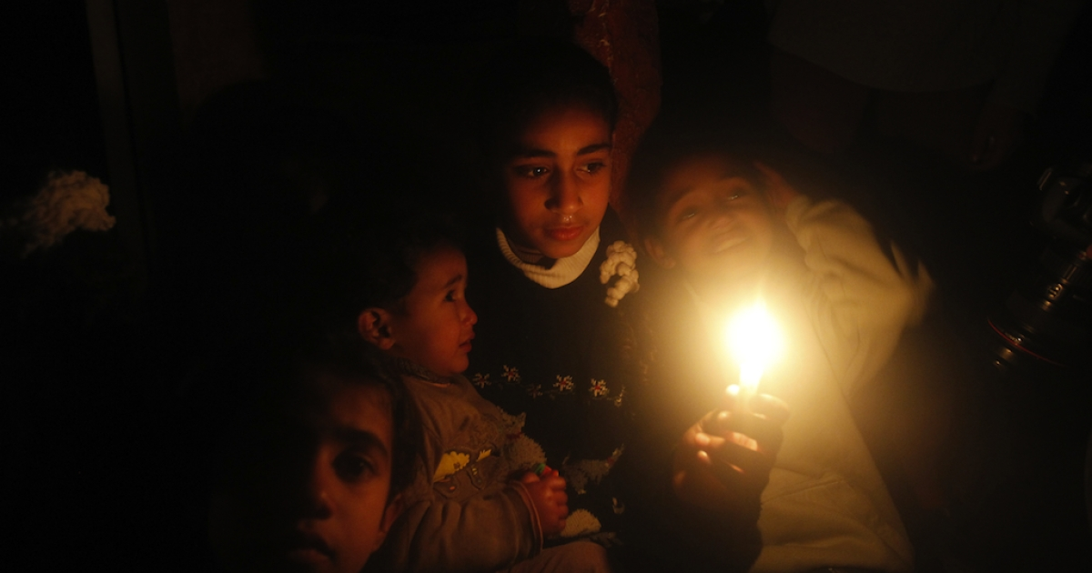Palestinian children sit at their home during a power cut at the Shati refugee camp in Gaza City earlier this month.</p>