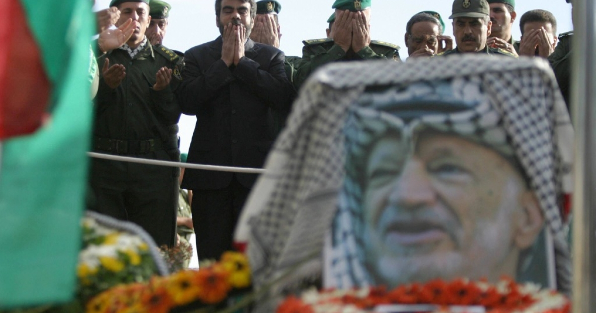 Palestinian officers pray around the grave of late Palestinian leader Yasser Arafat inside his Muqataa compound in the West Bank town of Ramallah 13 November 2004.</p>