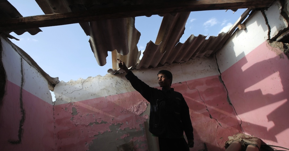 A Palestinian youth points to the damaged roof of a building following an Israeli military air strike in Rafah town in the southern Gaza Strip, on November 11, 2012. The flare-up which began November 10, was one of the most serious since Israel's devastating 22-day operation in the Gaza Strip over New Year 2009, has culminated in six Palestinians being killed and 32 injured by Israeli strikes after militants fired on an Israeli jeep, wounding four soldiers, medics and witnesses said.</p>