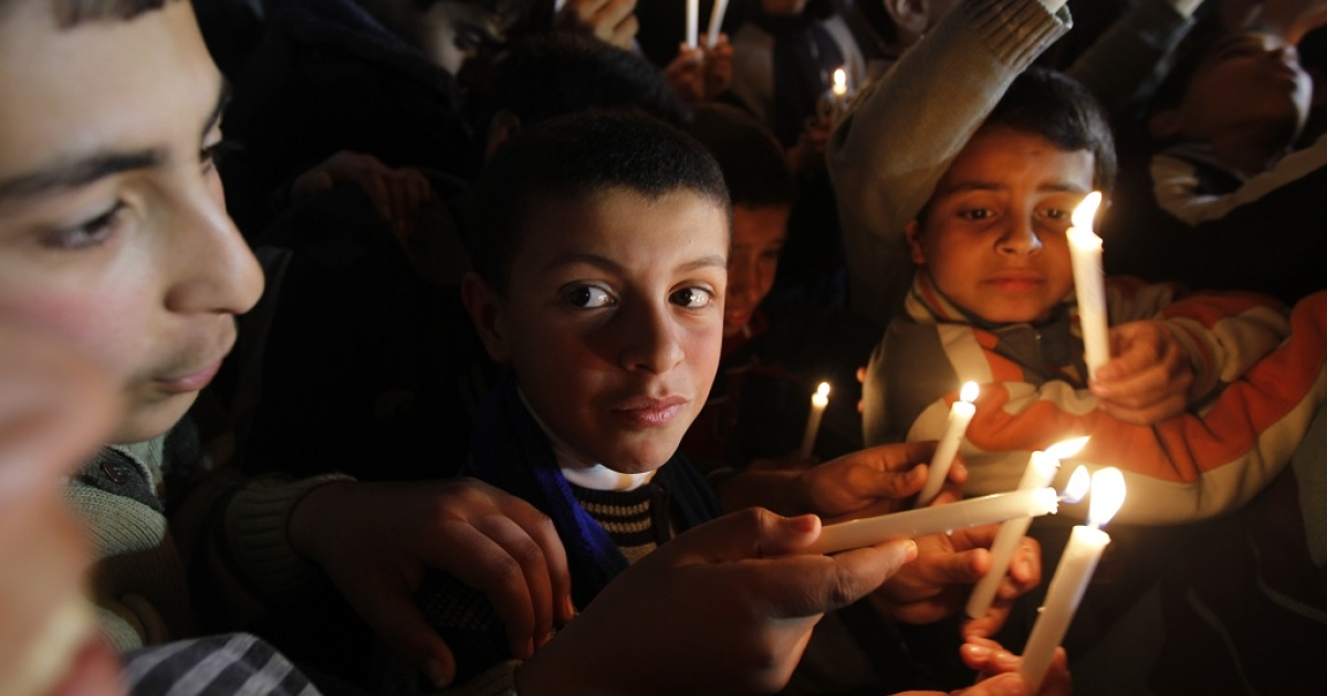 Palestinian schoolchildren hold up candles during a protest on Feb. 14 calling for a steady fuel supply for the Gaza Strip</p>