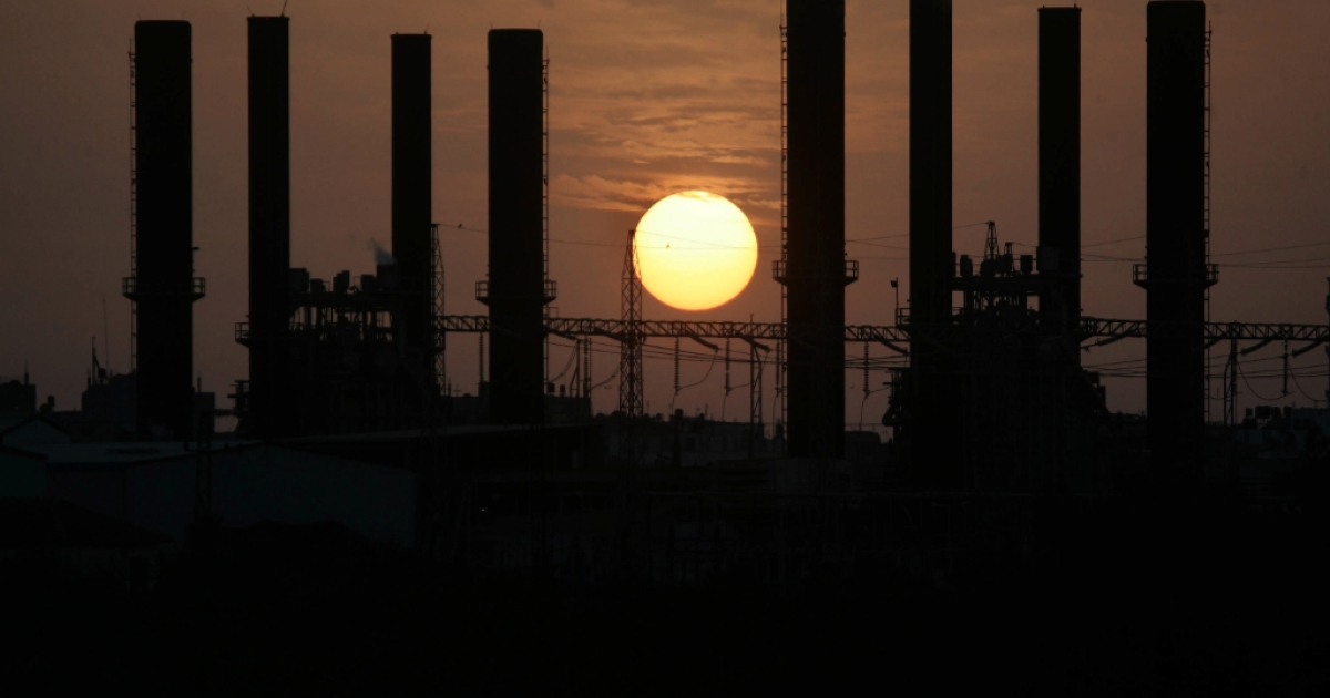 The sun sets next to the main Palestinian electricity company in Al-Nusairat, Gaza Strip.</p>