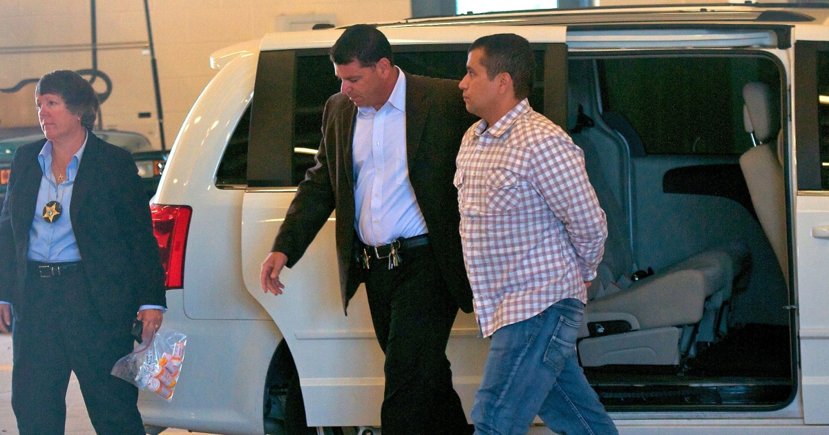 George Zimmerman (R) is escorted out of a van in to the Seminole County Jail as he surrenders to authorities June 3, 2012, two days after he had his bond revoked because of allegedly misleading the court about his finances. (Photo by Roberto Gonzalez/Getty Images)</p>