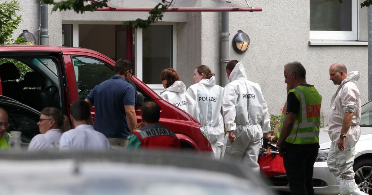 Members of the forensic police enter the house where a gunman had taken several people, including a bailiff, hostage during a home eviction in Karlsruhe, southwestern Germany, on July 4, 2012.</p>