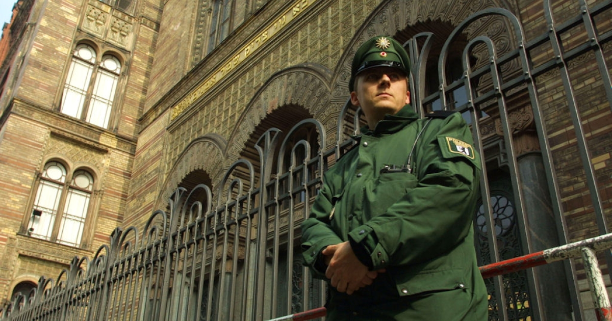 A police officer guards the Oranienburg Street Synagogue on April 26, 2002 in Berlin, Germany. German police have stepped up security around Jewish establishments in light of recent arrests in Germany of members of Al-Tawhid, a terrorist cell linked to Osama bin Laden.</p>