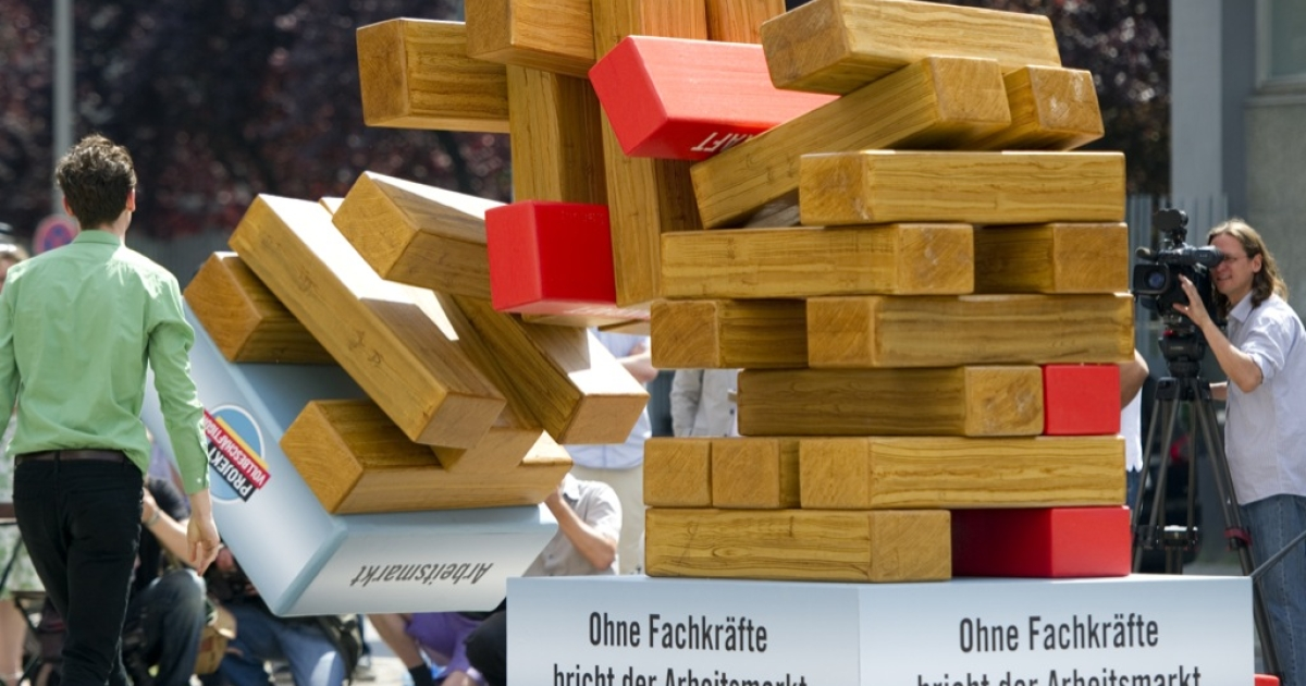 A tower symbolizing the labor market tumbles down after one of the red elements standing for skilled workers was pulled away on May 31, 2011 in Berlin. German unemployment fell to 7 percent of the workforce in May 2011, official data showed as the country continued to reap the benefits of labor market reforms and a global recovery.</p>