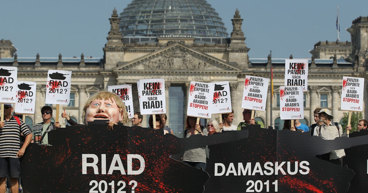 Activists hold signs that read 'Stop Tank Exports To Saudi Arabia!' and 'No Tanks To Riad!' as they stand behind effigies of tanks while protesting near the Reichstag on July 6, 2011 in Berlin, Germany.</p>