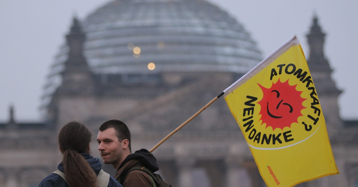 Anti-nuclear activists walk past the Reichstag following a demonstration on March 14, 2011 in Berlin, Germany.</p>