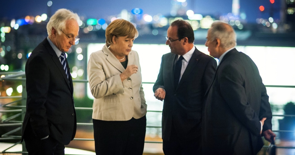 In Berlin, German Chancellor Angela Merkel speaks with new French President Francois Hollande next to two translators before a working dinner at the Chancellery hours after Hollande's inauguration in Paris on May 15, 2012.</p>