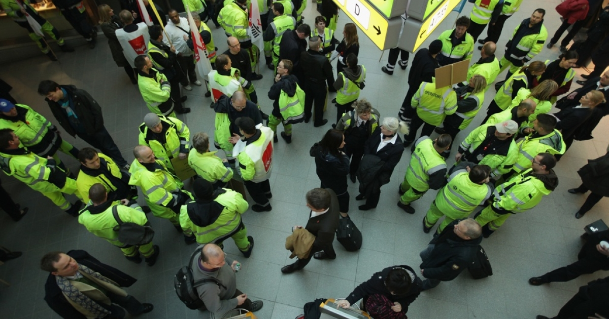 Striking ground personnel stand in the main hall at Tegel Airport on March 2 in Berlin.</p>