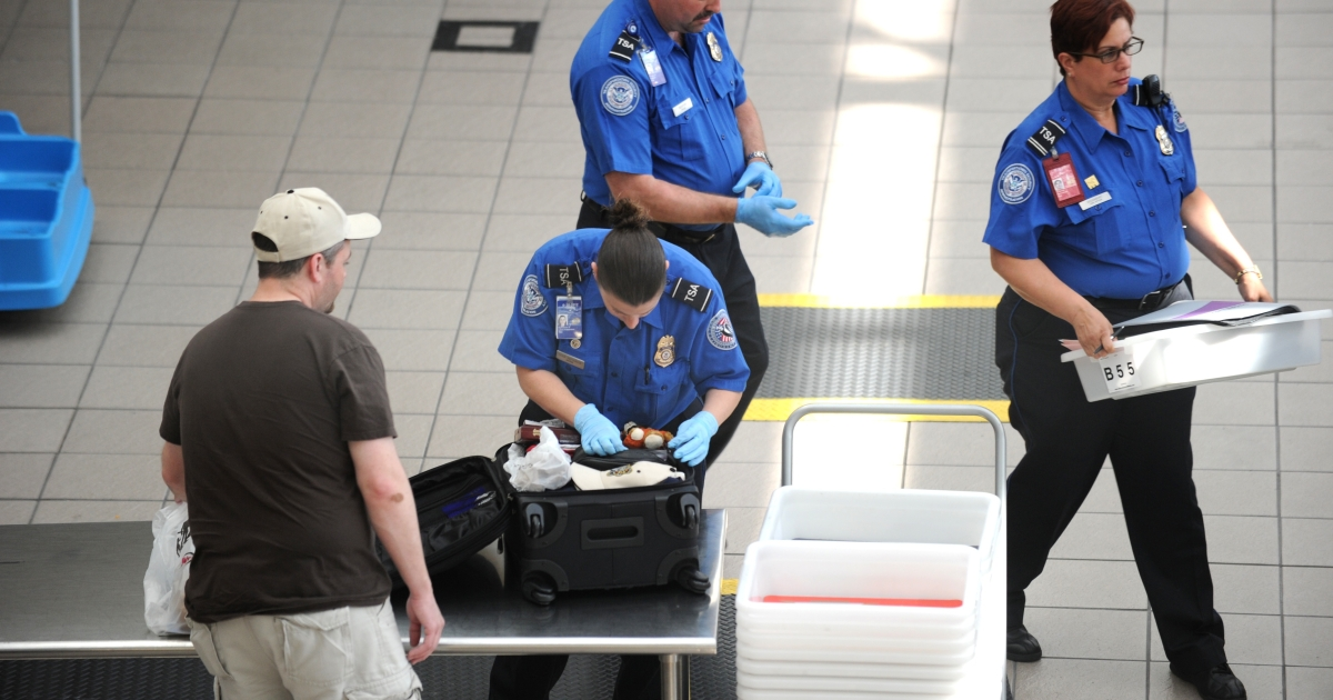 Transportation Security Administration agents check passengers' bags on May 2, 2011, at Orlando International Airport in Orlando, Fla.</p>