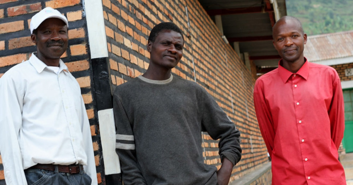 Gervais Twaherere stands with a potential vasectomy candidate and Charles Nkrunziza outside Mukono Health Center in Gicumbi, Rwanda</p>