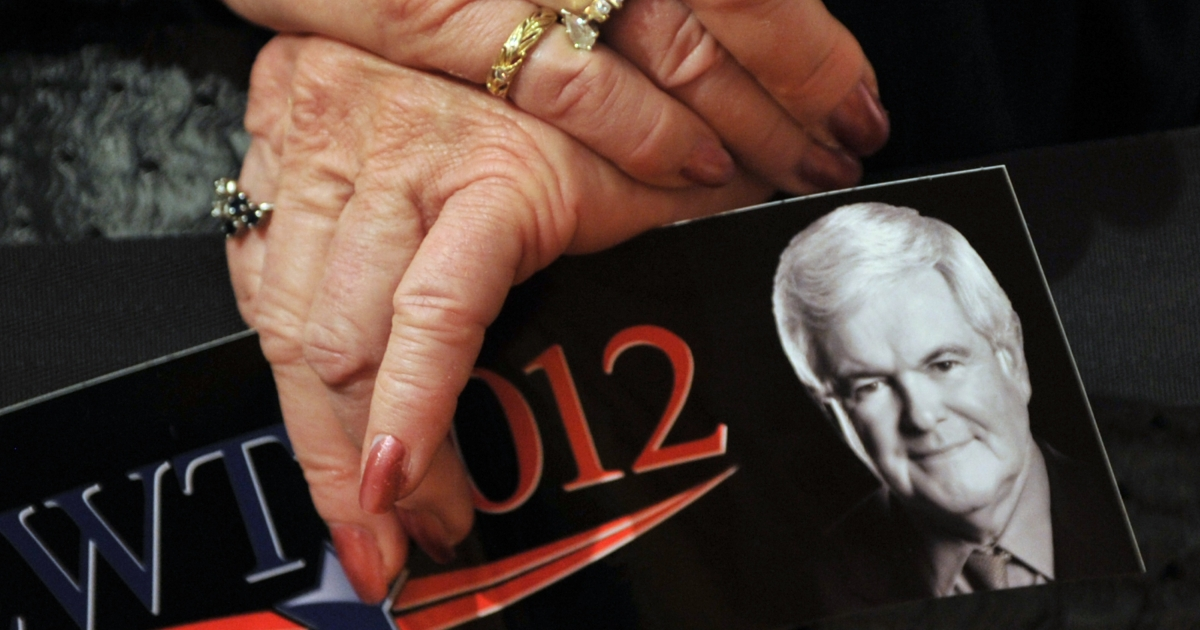 A supporter of Republican presidential hopeful Newt Gingrich holds a bumper sticker at a rally in Golden, Colorado.</p>