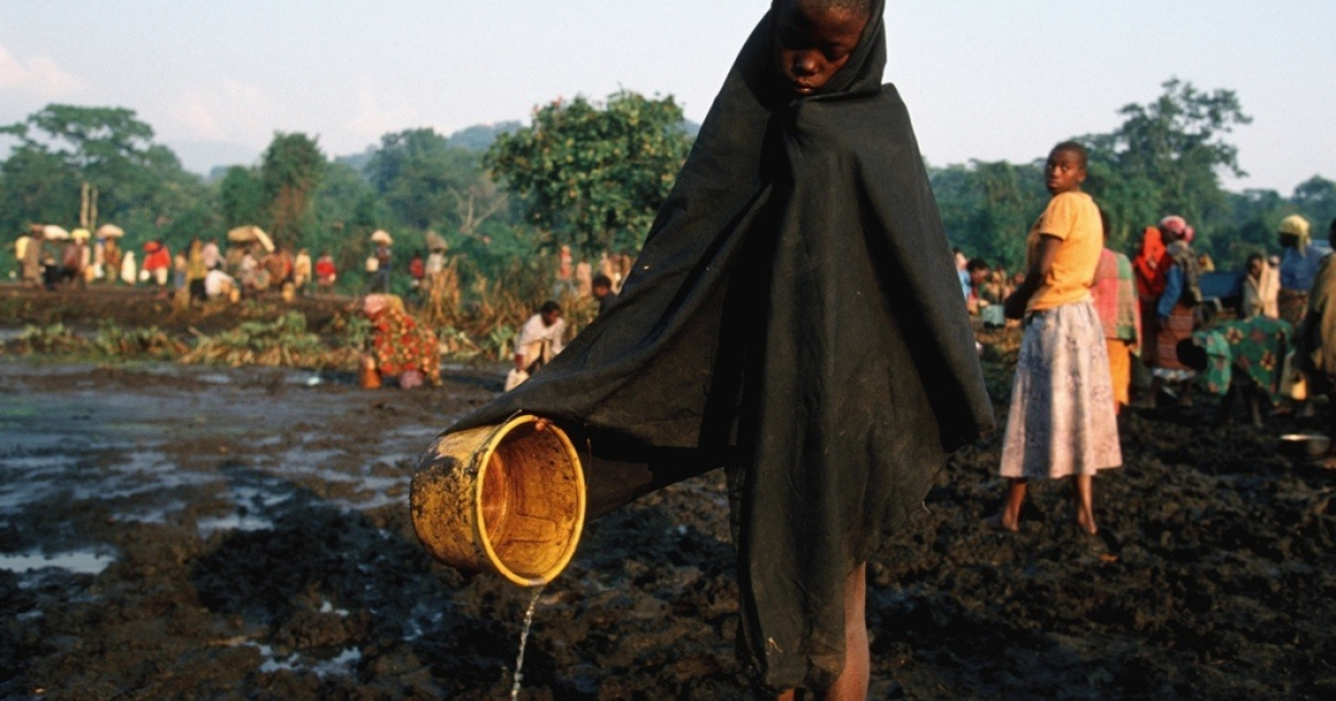 A Rwandan gathering polluted water at the largest refugee camp at Kitali, eastern Congo. Thousands of Hutus died of a cholera epidemic after escaping Rwanda where they were responsible for the killing of almost one million Tutsis.</p>
