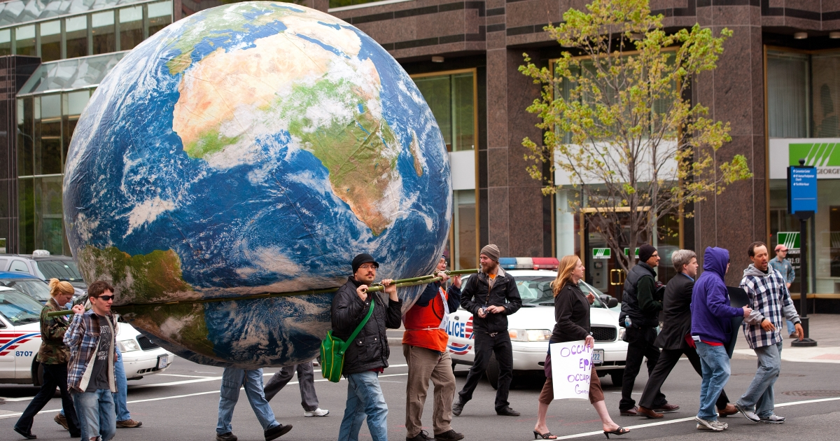 Occupy DC protesters carry a globe through the streets of Washington on their way to protest in front of the Environmental Protection Agency (EPA) on March 30, 2012.</p>
