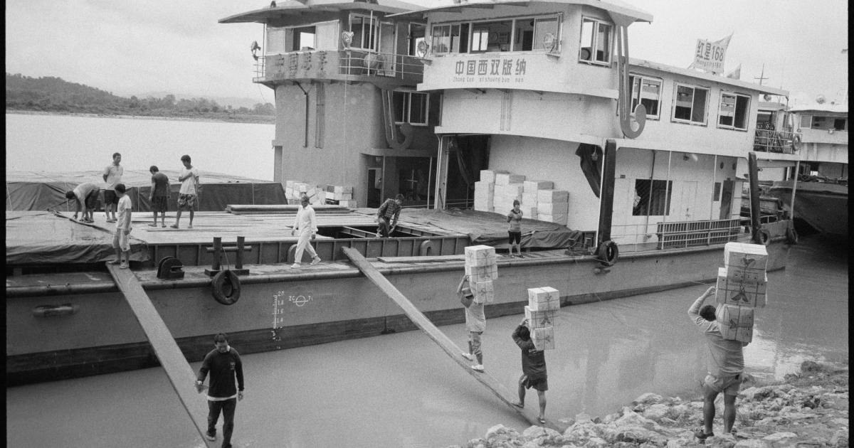 Thai workers load produce onto a Chinese ship on the Mekong River. In 2011 pirates attacked two Chinese ships and killled the crew. China now operates its own naval gunboats in Lao and Burmese waters to protect its shipping.</p>
