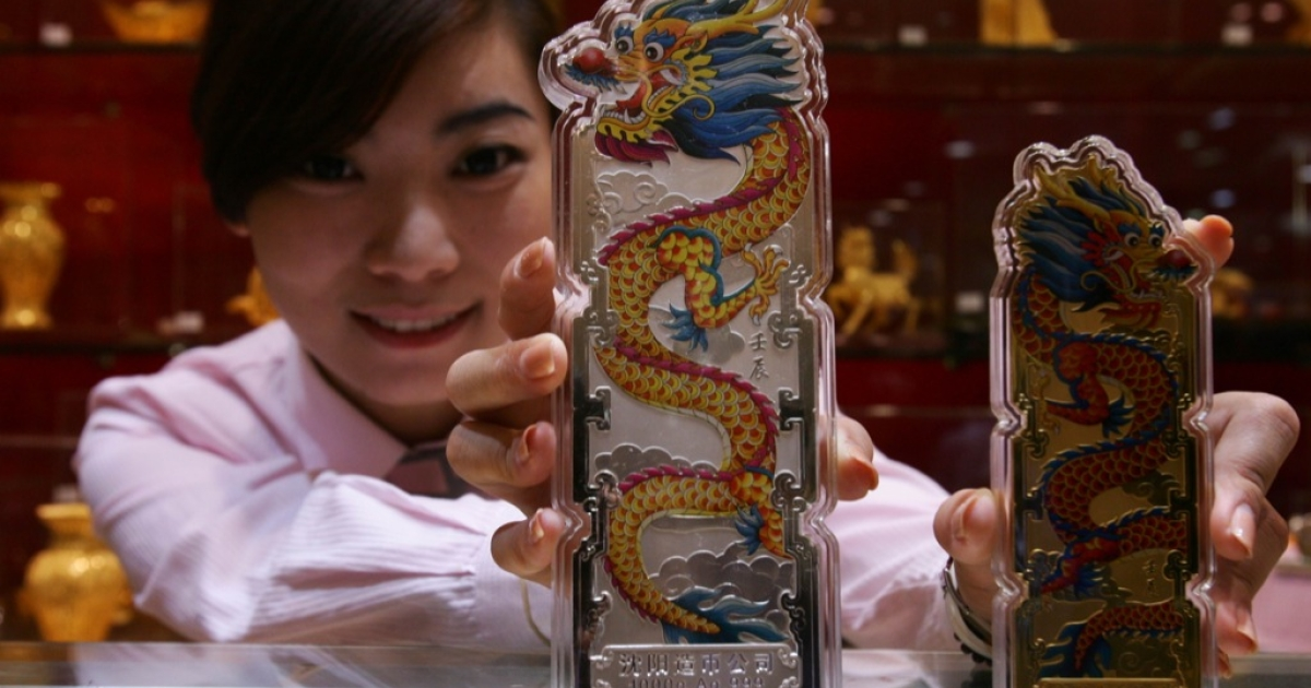 An employee shows off silver and gold bullion bars engraved with dragons at a gold shop in Beijing on September 15, 2011.</p>