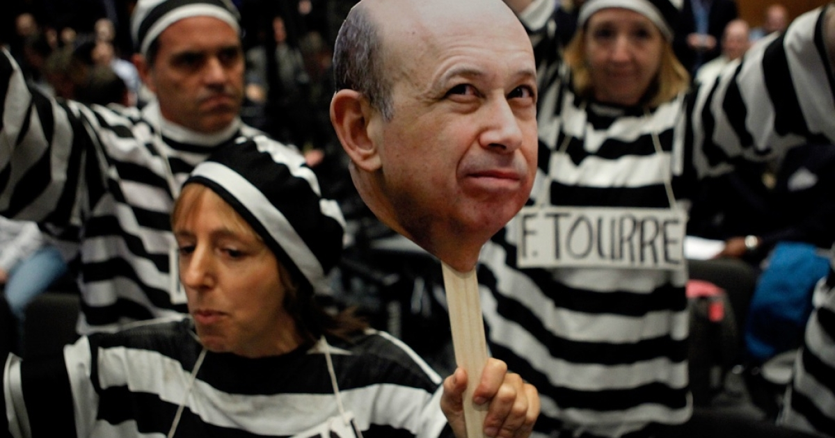 Demonstrators from Code Pink for Peace hold photographs of Lloyd Blankfein, chairman and CEO of The Goldman Sachs Group, and demand he be jailed with other executives before a hearing of the Senate Homeland Security and Governmental Affairs Investigations Subcommittee on Capitol Hill on April 27, 2010 in Washington, DC.</p>