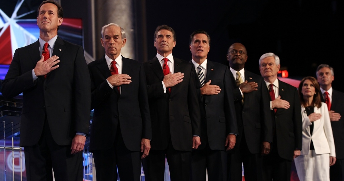 Republican presidential candidates (L-R) Rick Santorum, Rep. Ron Paul (R-TX), Texas Gov. Rick Perry, Mitt Romney, Herman Cain, Newt Gingrich, Rep. Michele Bachmann (R-MN), and Jon Huntsman place their hands over their hearts during the national anthem prior to a debate at Constitution Hall November 22, 2011 in Washington, DC.</p>