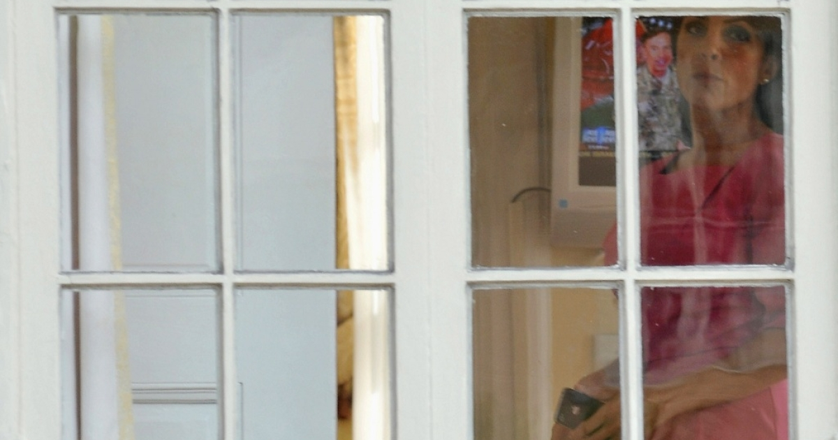Jill Kelley looks out the window of her home as Gen. David H. Petraeus is seen on the television in the background on November 13, 2012 in Tampa, Florida. Kelley, who is reported to be involved with the military community at MacDill Air Force Base, reported receiving harassing emails to the FBI, which resulted in an investigation that revealed the sender to be Paula Broadwell, who was found to be having an affair with Gen. David H. Petraeus.</p>