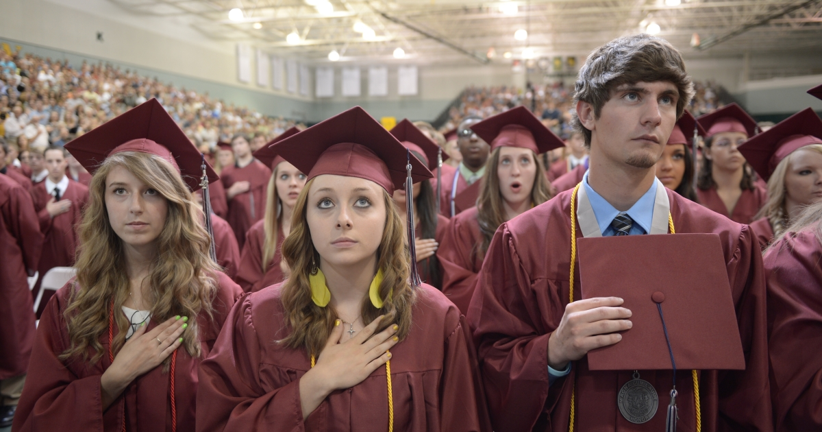 Students listen to then national anthem prior to US President Barack Obama's delivering of the commencement address on May 21, 2012 at Missouri Southern State University in Joplin, Missouri.</p>