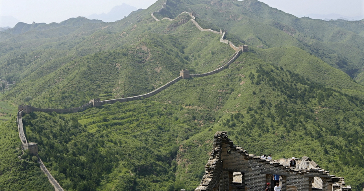 Tourists climb up a dilapidated section of the Great Wall of China, at Simatai, northeast of Beijing, 1 July 2007. This Ming-dynasty Wall was built as one of four major strategic strongholds for defensive puropses from tribes invading from the north.</p>