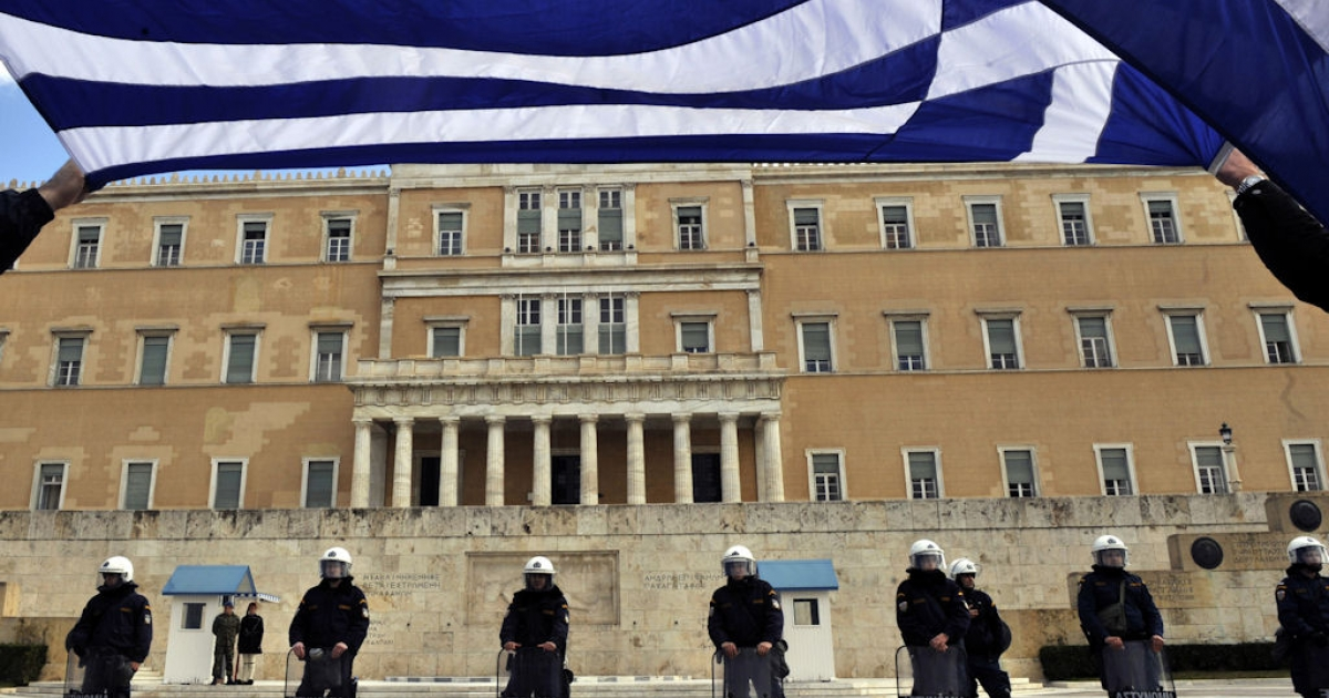 Holding a Greek flag bus employees protest in front of the Greek Parliament in Athens on Feb. 1, 2011.</p>