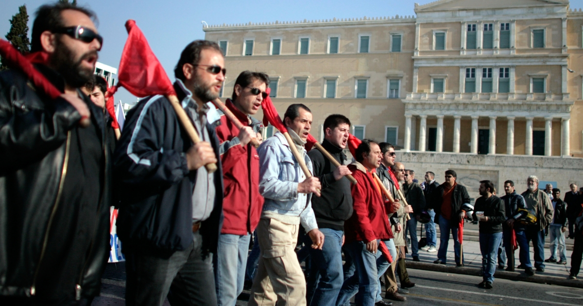 Demonstrators protesting austerity measures march in front of the parliament building during a rally in Athens, Greece, on Dec. 1, 2011.</p>