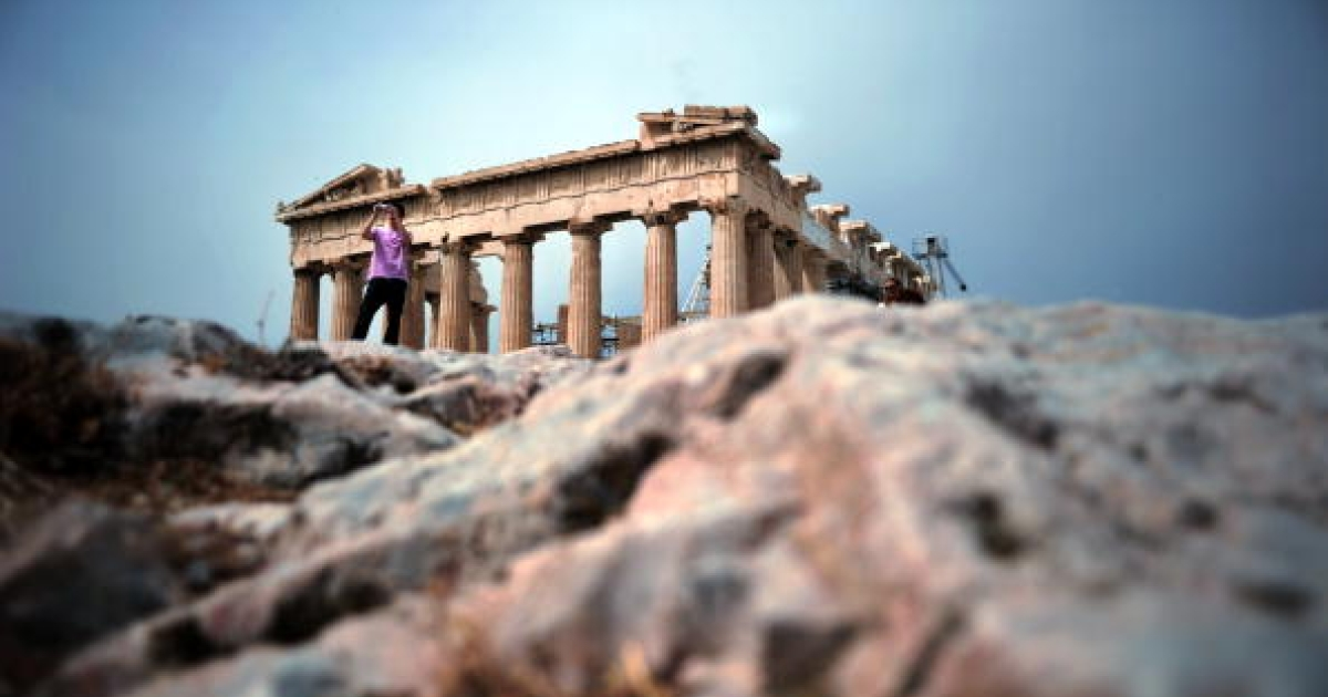 A tourist takes pictures at the Acropolis archeological site in Athens on May 8, 2010.</p>