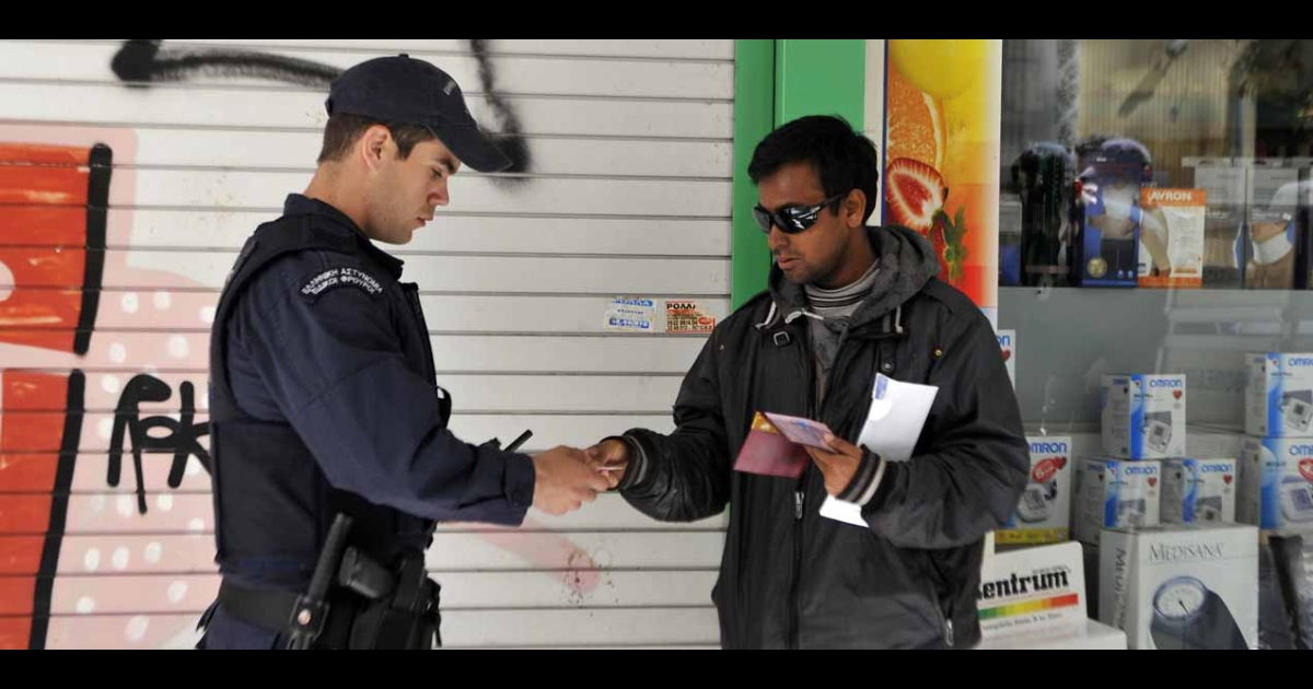 Police check an immigrant's papers in central Athens' Omonia square area, March 29, 2012.</p>