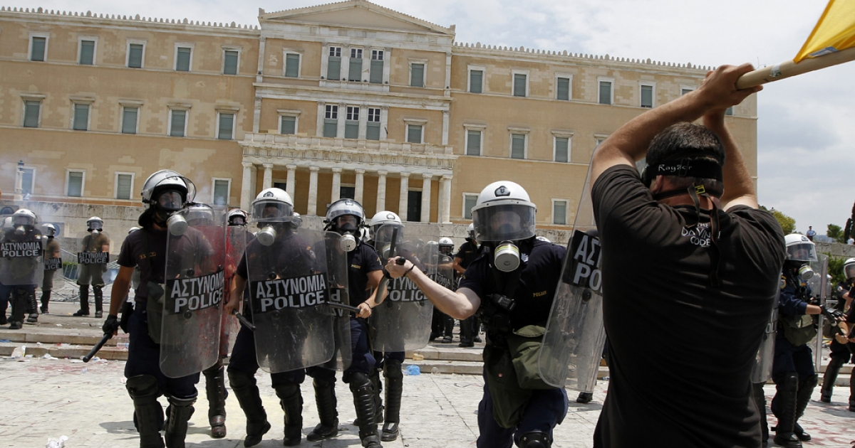 Protesters clash with riot police in front of the Greek Parliament on June 29, 2011 in Athens, as lawmakers voted on a massive austerity package demanded by international creditors.</p>