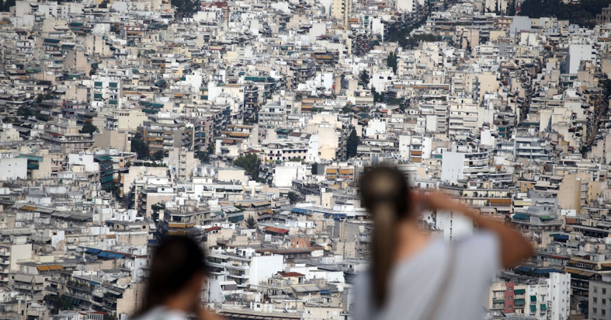 Two tourists take pictures of Athens, Greece from Mount Lycabettus on June 1, 2011.</p>