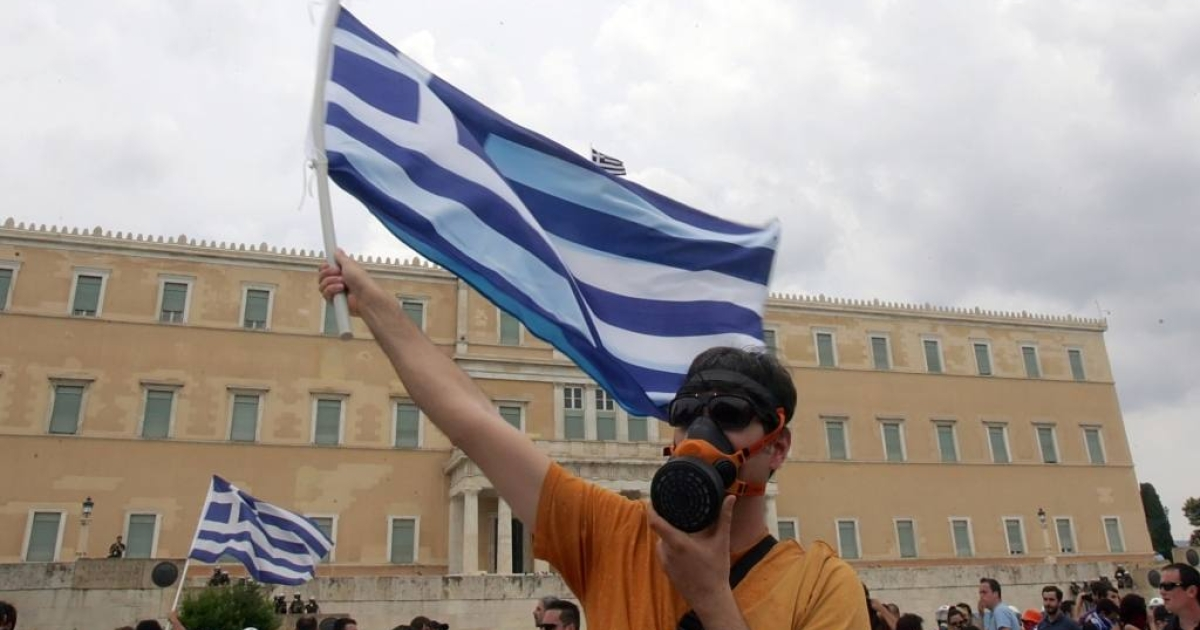 A demonstrator protesting the government's austerity program waves a Greek flag outside of parliament.</p>