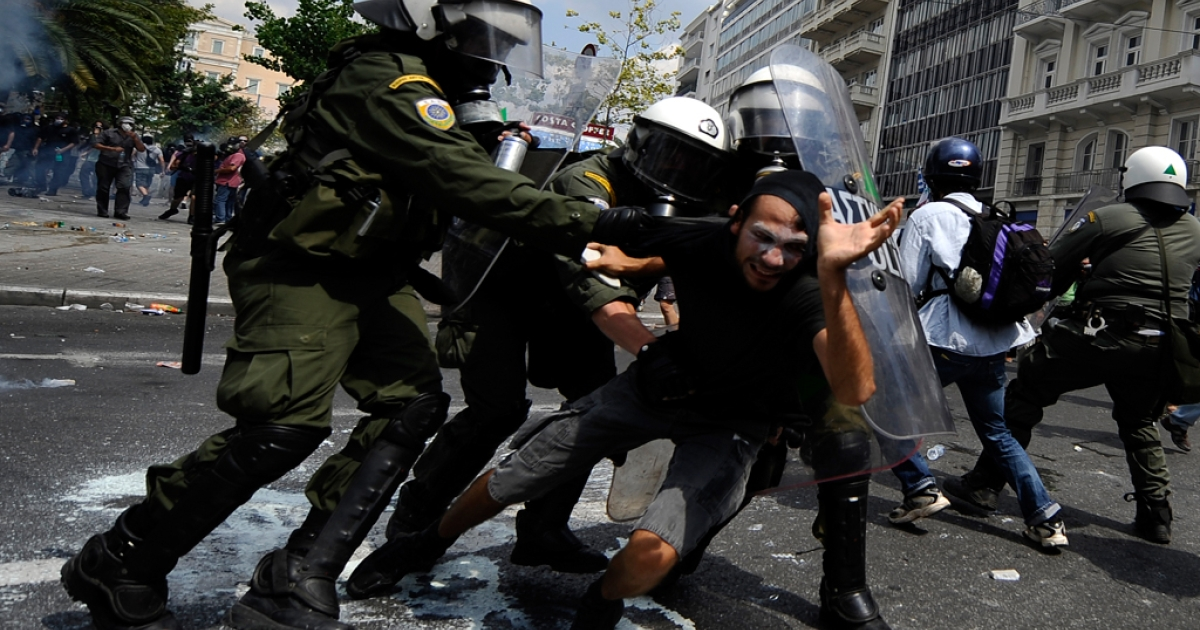 A demonstrator is grabbed by riot police during clashes near the Greek parliament on June 28, 2011 in Athens during a protest part of the 48-hour general strike against the bankruptcy-threatened government which pushed through sweeping austerity cuts.</p>