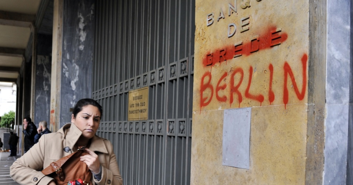A woman passes by the Bank of Greece headquarters where 'Greece' was changed to 'Berlin' during a 24-hour general strike in Athens on February 7, 2012, in protest against new austerity measures demanded with increasing urgency by the European Union as part of a debt rescue deal with banks.</p>