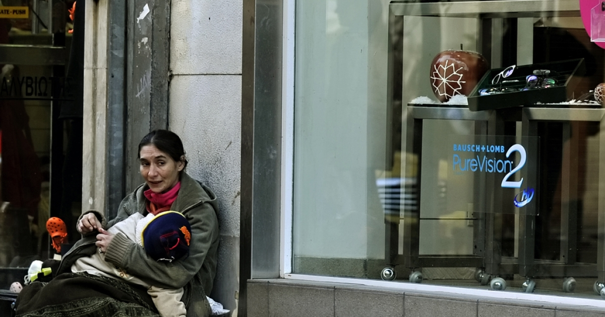 A woman holds her child as she begs outside shops displaying Christmas offers in central Athens on December 9, 2011. Greece's economy remained trapped in a deep recession in the third quarter but shrank less than previously thought, at a revised 5.0 percent from an initial 5.2 percent, official figures showed today.  AFP PHOTO / LOUISA GOULIAMAKI</p>